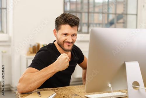 Fototapeta mann schaut auf seinen pc und ballt zufrieden die faust