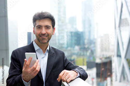 Attractive middle aged business man checking email on his smartphone on the way Poster