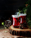 glass of hot mulled wine for the new year with ingredients for cooking, nuts and Christmas decorations - 180961452