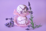 bath bomb with lavender extract. two  lilac lavender bombs and twigs of lavender flowers on a bright purple background. Organic Botanical Body Care - 180965202