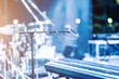 Microphone and synthesizer on concert stage with defused bokeh lights blue colour background