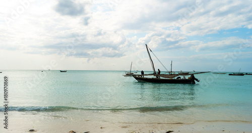Poster Zanzibar Old rustic fishing boat sitting in the ocean, calm and still turquoise waters, zanzibar