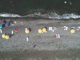 Aerial view of yellow umbrellas on pebble beach. Small waves on the water. Top view.