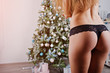 Gorgeous sexy womans back buttocks at black underwear posed at studio against new year tree with decoration and gifts. Christmas holidays theme.