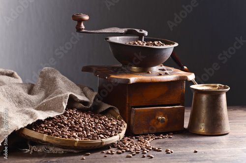 Old coffee grinder and roasted coffee beans on wooden table
