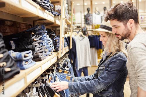 Plakat Junges Paar im Jeans Mode Shop beim Einkaufen