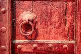 Old doorknob on vintage red door in India