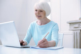 Progressive pensioner. Active progressive cheerful old woman looking happy while working at her laptop - 180990812