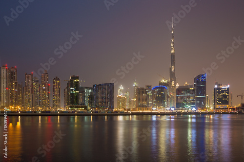 DUBAI, UAE - MARCH 23, 2017: The evening panorama over the new Canal with the Downtown and Burj Khalifa tower Poster