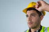 Male architect holding hard hat against white background - 180994616