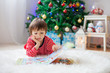 Cute boy, reading a book in front of Christmas tree