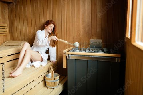 Fotobehang Spa Beautiful woman in sauna pouring oils on hot stones