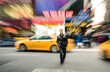 Radial blur of yellow taxicabs and unidentified person walking on 42nd street crossroad in Manhattan downtown district - Everyday commuting life New York City on rush hour in urban business area