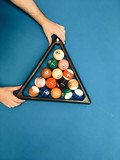Puramid of pool billiard balls in hands on blue table