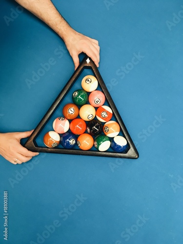 Puramid of pool billiard balls in hands on blue table