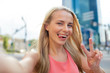 happy young woman taking selfie on city street - 181016801