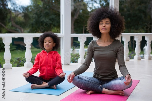 Mother and daughter meditating together in the porch