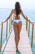 Beautiful woman in white bikini goes ahead