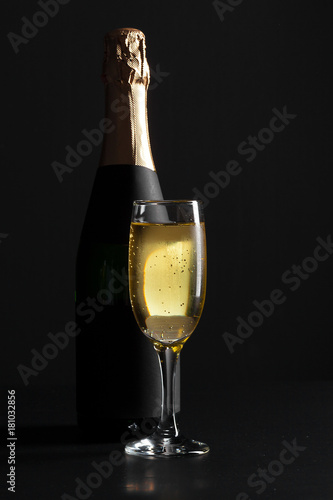 Plakat champagne wine glass and bottle on black background