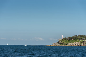 Sydney, Australia - March 26, 2017: South Head clliffs with Hornby lighthouse at entrance to the bay from Tasman Sea under open blue sky and dark blue sea water. Some yachts in distance.