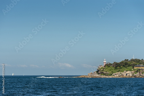 Poster Sydney Sydney, Australia - March 26, 2017: South Head clliffs with Hornby lighthouse at entrance to the bay from Tasman Sea under open blue sky and dark blue sea water. Some yachts in distance.
