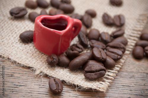 Fotobehang Koffiebonen grains de café et tasse en forme de coeur sur table en bois