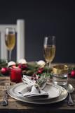 Tavola apparecchiata natalizia con bicchieri di spumante. Tema cibo e feste - 181040647