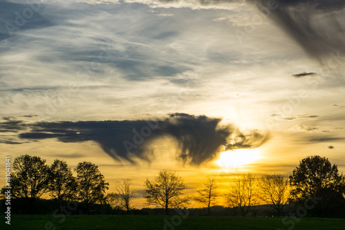 Papiers peints Morning Glory Orange sky with dramatic clouds as sunset on landscape with wide meadow and trees