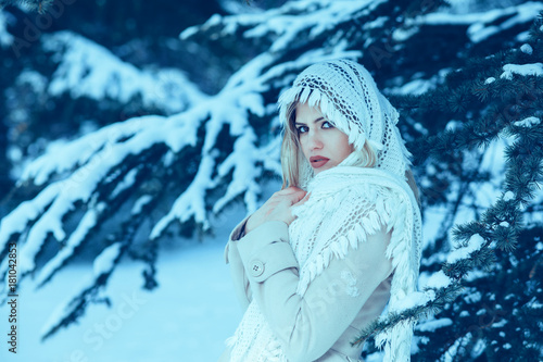 Portrait of a young beautiful woman in white winter forest