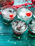 Christmas party green alcohol drinks with cherry. Festive aperitif shots and ornaments on wooden dark table. Holiday background with falling snow - 181043281