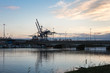 Container Terminal, Shipyard and Cranes at Sunset and Their Refl