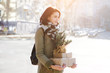 Outdoor portrait of beautiful happy smiling young woman with Christmas gifts on street.