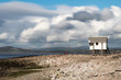 An elevated hut looks out over a pebble beach towards the Morecambe Bay, Lancashire with rolling clouds above. This is a panorama stitch of 5 images.
