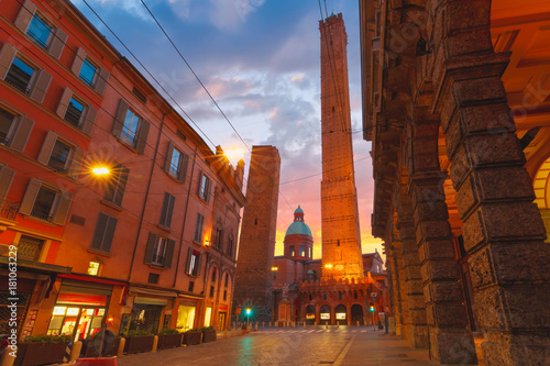 Two Towers, Asinelli and Garisenda, both of them leaning, symbol of Bologna, statue of San Petronius and Church of Saints Bartholomew and Gaetano at sunrise, Bologna, Emilia-Romagna, Italy