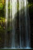 Man under sunlit waterfall (Northern Australia)