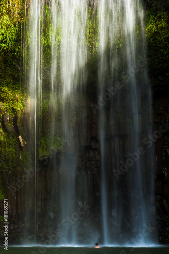 Man under sunlit waterfall (Northern Australia)
