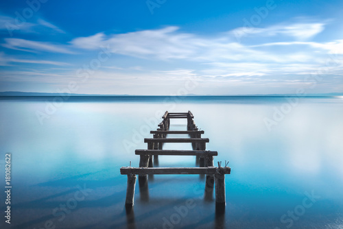 Aluminium Pier Wooden pier or jetty remains on a blue lake. Long Exposure.