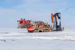 self-propelled drilling rig and pump jack in winter time on the field with snow