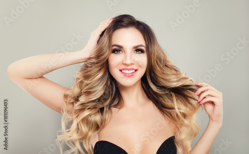 Glamorous Blonde Woman with Perfect Hairstyle and Makeup. Beautiful Model with Long Curly Hair Smiling