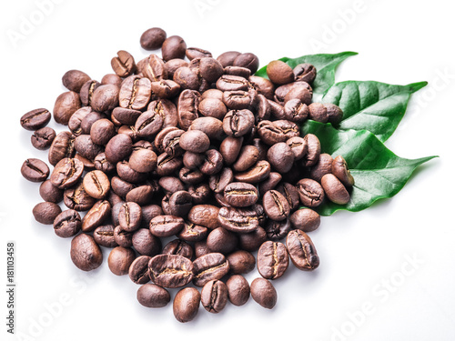 Roasted coffee beans and leaves on white background.