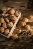 Fresh nuts in a crate on straw background - 181112864