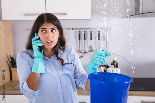 Woman Calling Plumber While Collecting Water