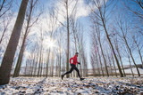 Man running on the snow in a forest - 181133059