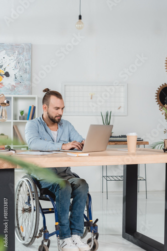 Sticker man on wheelchair working with laptop