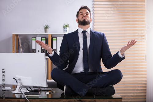 Naklejka Businessman Doing Yoga In Office