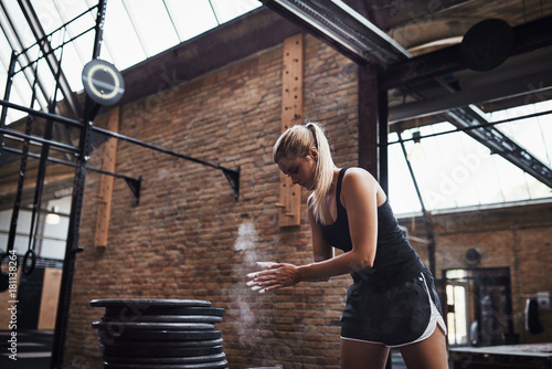 Young woman chalking up before lifting weights in a gym