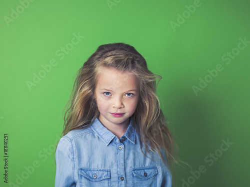 young beautiful girl in front of green background in the studio Poster