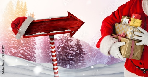 Santa holding gifts and Wooden signpost in Christmas Winter