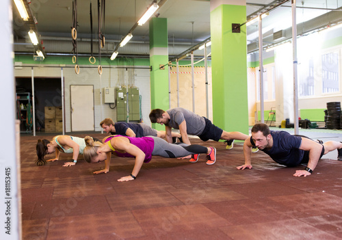 Wall mural group of people doing push-ups in gym