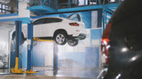 Mechanic in car service is washing luxury SUV under bottom in the suds by water hoses - 181153807